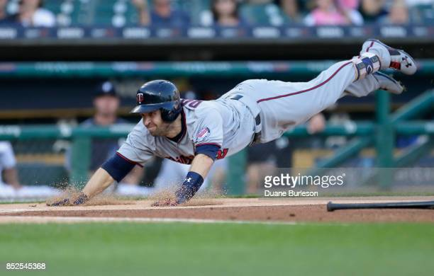 Brian Dozier of the Minnesota Twins dives into home plate to score on a bunt grounder and a throwing error by third baseman Jeimer Candelario of the...
