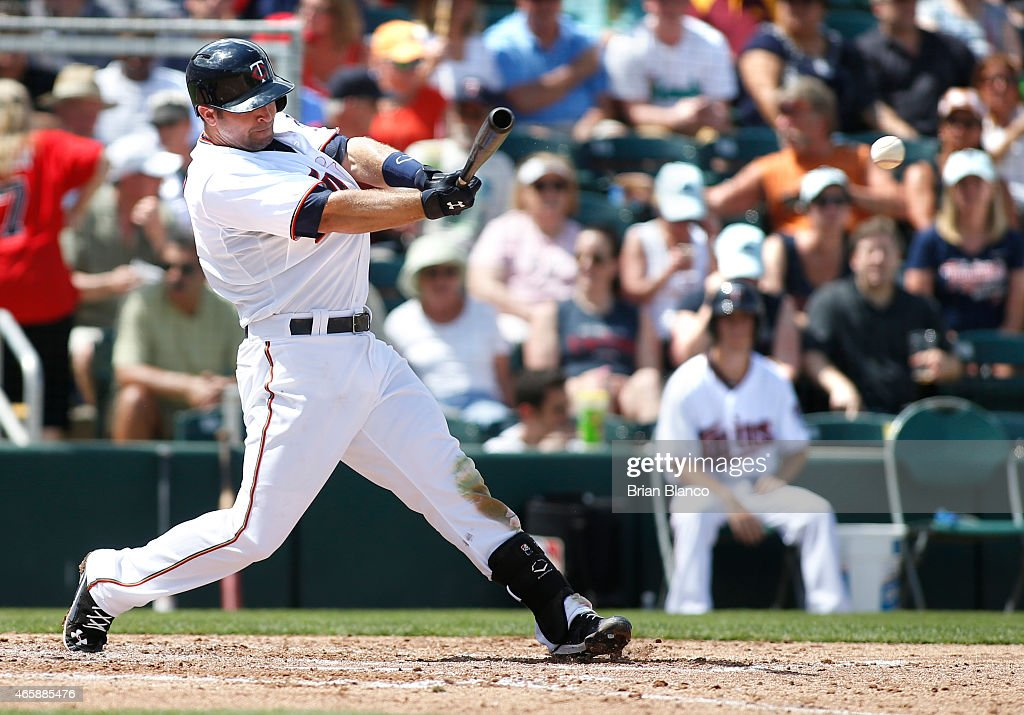 Brian Dozier of the Minnesota Twins hits a single during the third inning of a spring training game against the Tampa Bay Rays on March 11 2015 at...
