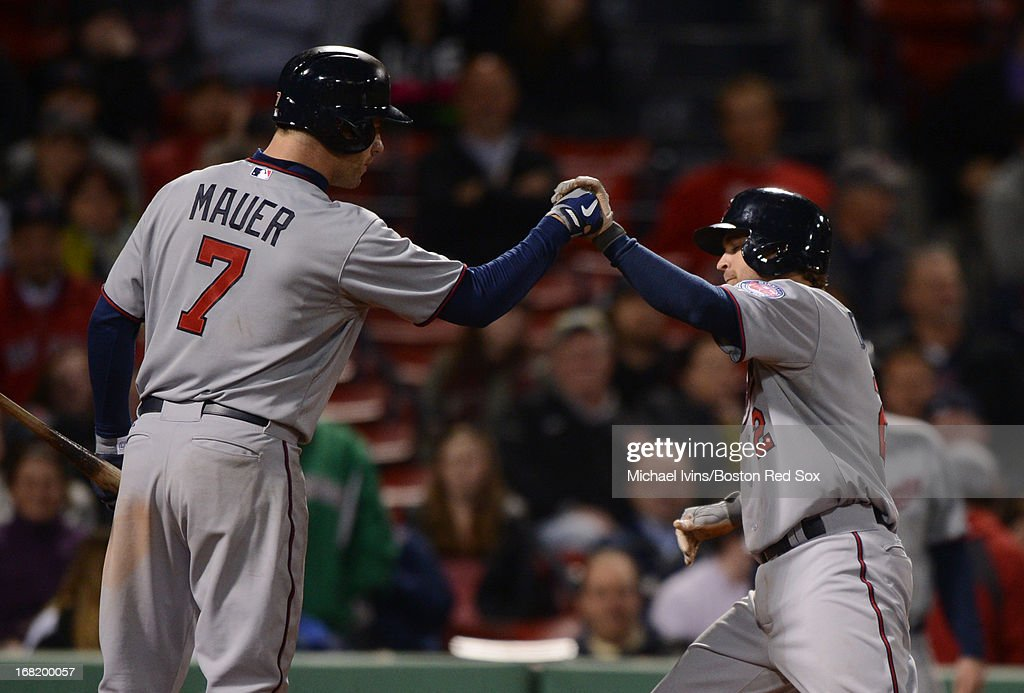 Brian Dozier #2 of the Minnesota Twins is congratulated by Joe Mauer #7 after hitting a home run against the Boston Red Sox in the ninth inning on May 6, 2013 at Fenway Park in Boston, Massachusetts.