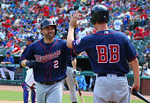 Brian Dozier of the Minnesota Twins is congratulated by the batboy for hitting a solo home run in the seventh inning against the Texas Rangers at...