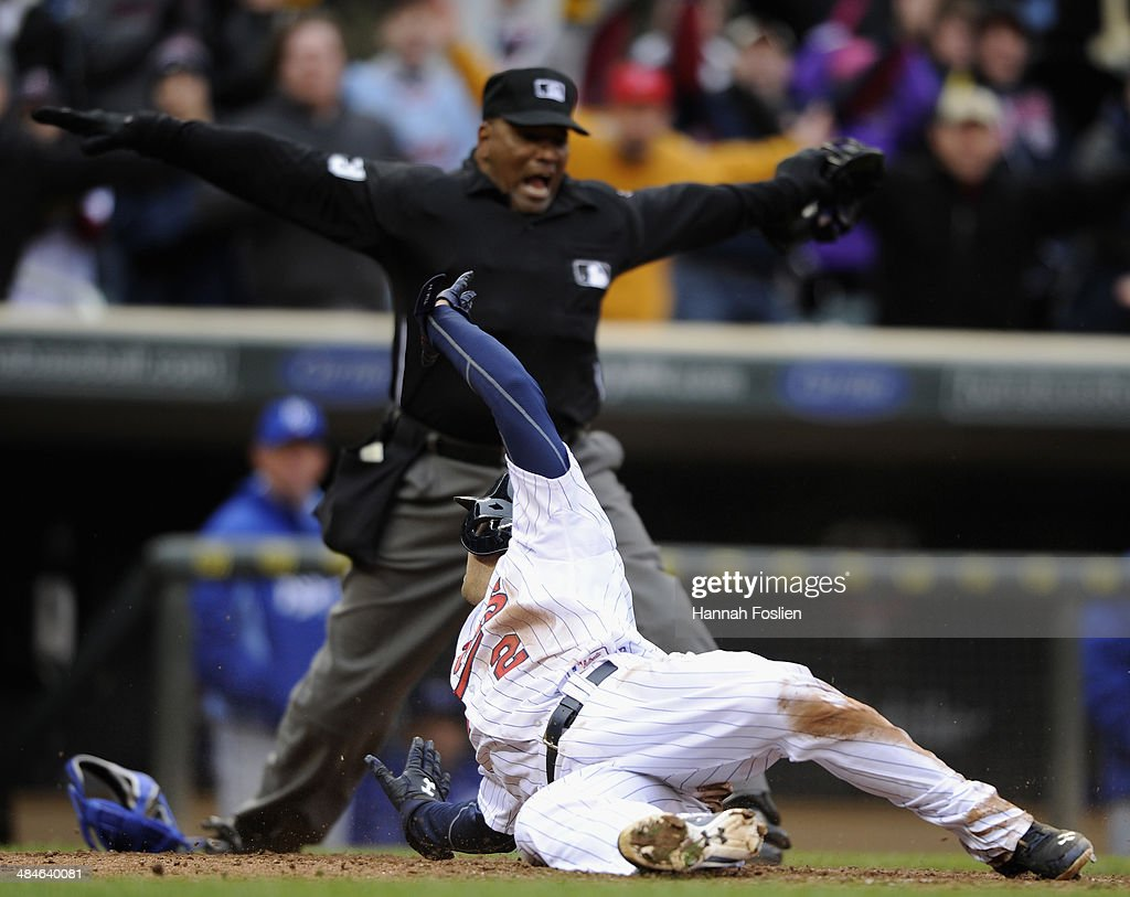 Brian Dozier of the Minnesota Twins looks on as home plate umpire Laz Diaz calls him safe during the eighth inning of the game against the Kansas...