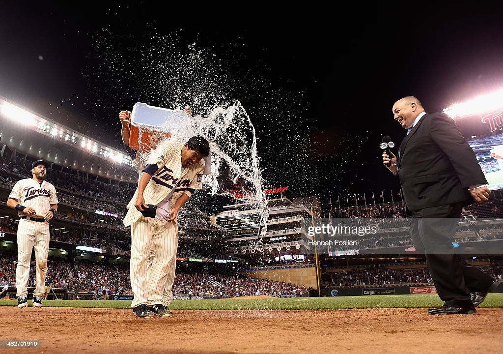 Brian Dozier of the Minnesota Twins pours wate on teammate Kurt Suzuki as Trevor Plouffe and Kevin Gorg of Fox Sports North look on after a walkoff...