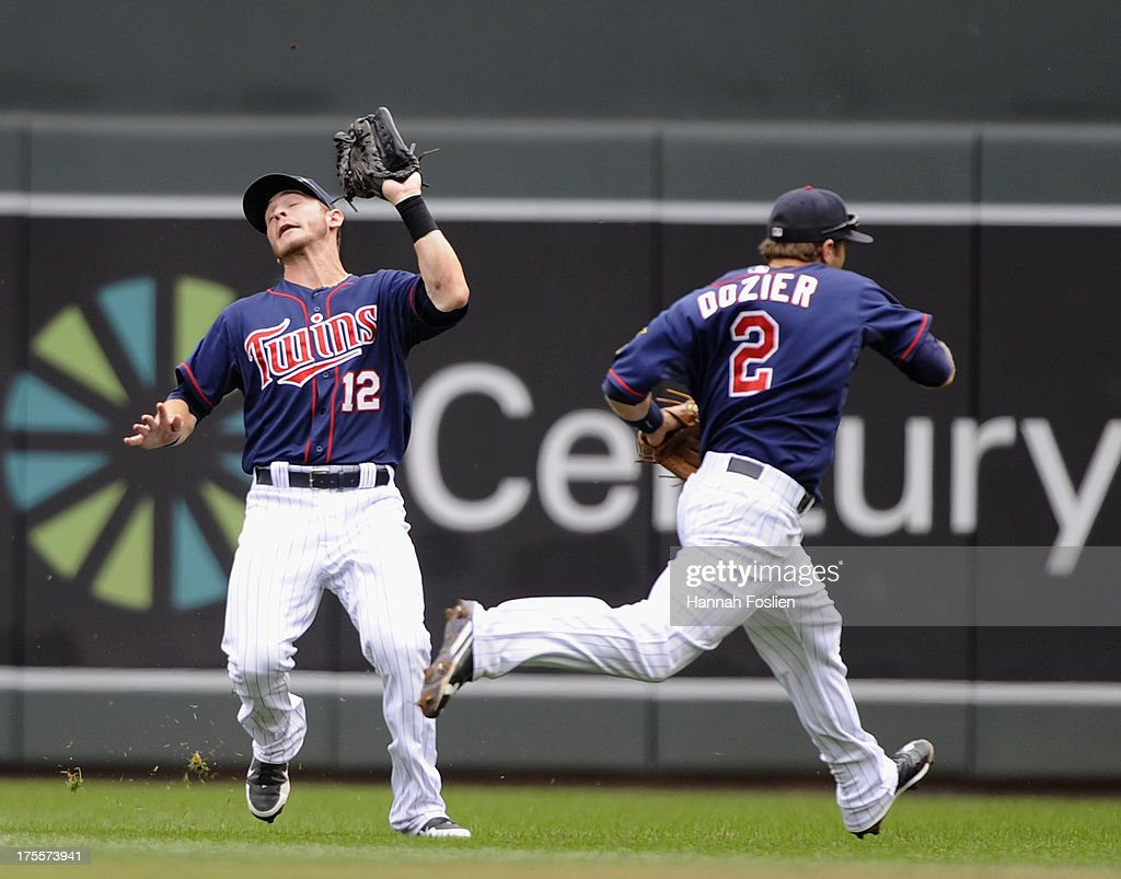 Brian Dozier #2 of the Minnesota Twins runs out of the way as teammate Chris Herrmann #12 makes a catch during the fourth inning of the game against the Houston Astros on August 4, 2013 at Target Field in Minneapolis, Minnesota.