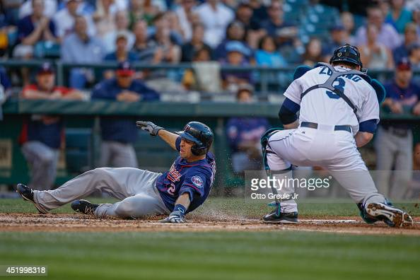 Brian Dozier of the Minnesota Twins scores on a sacrifice fly off the bat of Kurt Suzuki in the third inning against catcher Mike Zunino of the...