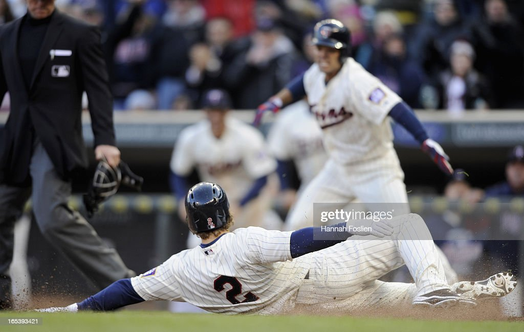 Brian Dozier #2 of the Minnesota Twins slides across home plate to score the winning run of the game against the Detroit Tigers during the ninth inning on April 3, 2013 at Target Field in Minneapolis, Minnesota. The Twins defeated the Tigers 3-2.
