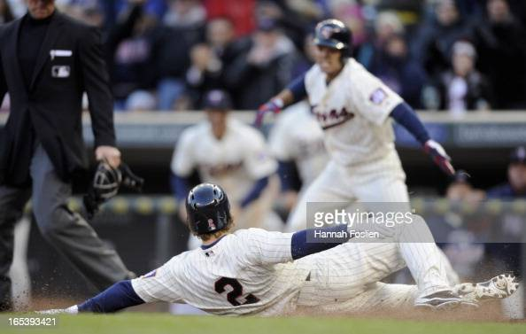 Brian Dozier of the Minnesota Twins slides across home plate to score the winning run of the game against the Detroit Tigers during the ninth inning...