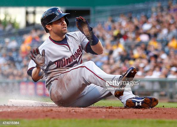 Brian Dozier of the Minnesota Twins slides safely into home plate in the second inning against the Pittsburgh Pirates during the game at PNC Park on...