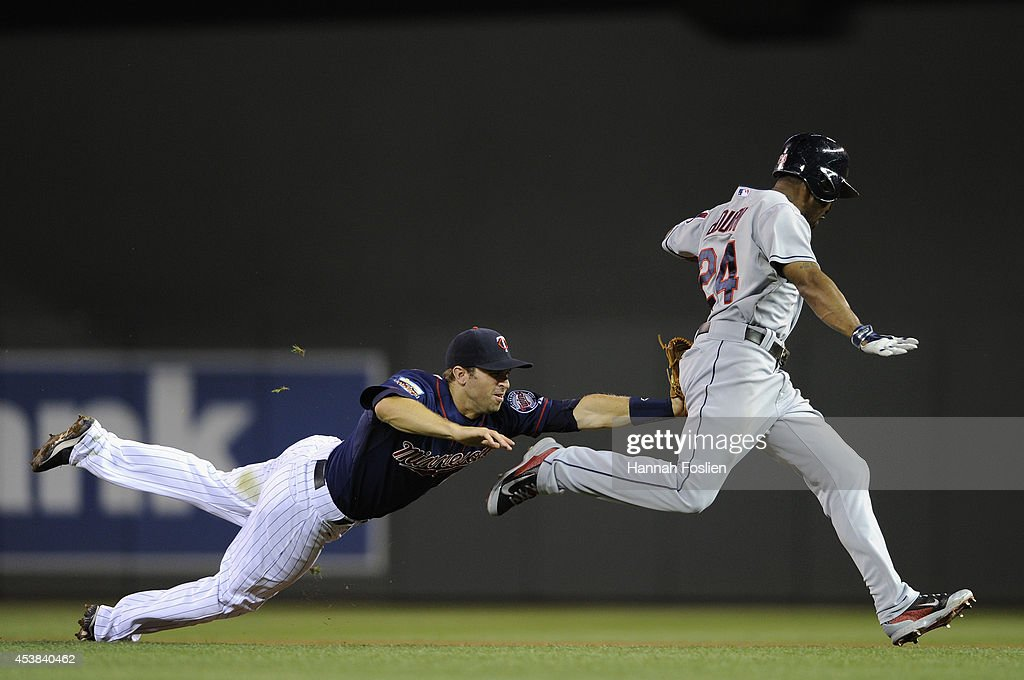 <a gi-track='captionPersonalityLinkClicked' href=/galleries/search?phrase=Brian+Dozier&family=editorial&specificpeople=7553002 ng-click='$event.stopPropagation()'>Brian Dozier</a> #2 of the Minnesota Twins tags out <a gi-track='captionPersonalityLinkClicked' href=/galleries/search?phrase=Michael+Bourn&family=editorial&specificpeople=835742 ng-click='$event.stopPropagation()'>Michael Bourn</a> #24 of the Cleveland Indians during a rundown between first and second base during the sixth inning of the game on August 19, 2014 at Target Field in Minneapolis, Minnesota. The Indians defeated the Twins 7-5.