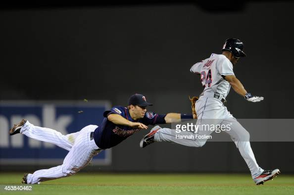 Brian Dozier of the Minnesota Twins tags out Michael Bourn of the Cleveland Indians during a rundown between first and second base during the sixth...