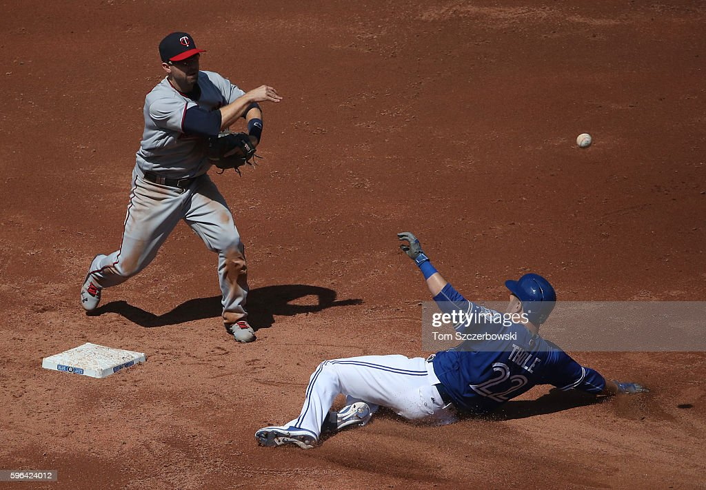 Brian Dozier of the Minnesota Twins turns a double play to end the third inning during MLB game action as Josh Thole of the Toronto Blue Jays slides...