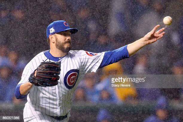Brian Duensing of the Chicago Cubs commits an error throwing to first base in the ninth inning during game four of the National League Division...