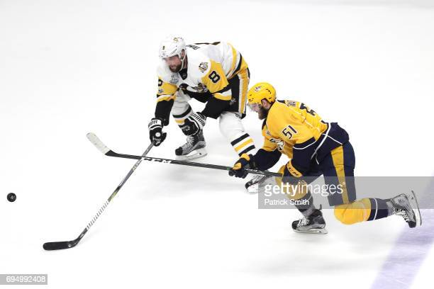 Brian Dumoulin of the Pittsburgh Penguins and Austin Watson of the Nashville Predators battle for the puck during the second period in Game Six of...