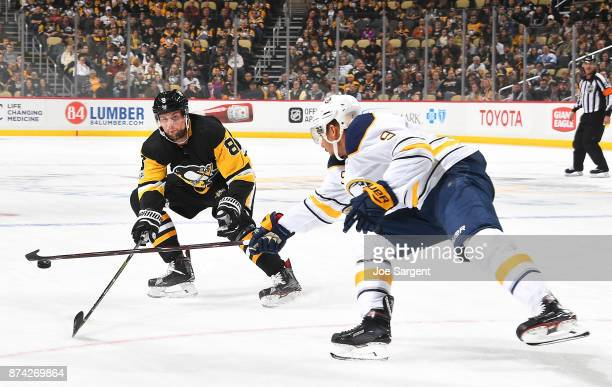 Brian Dumoulin of the Pittsburgh Penguins and Evander Kane of the Buffalo Sabres battle for the puck at PPG Paints Arena on November 14 2017 in...