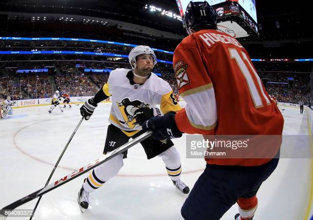 Brian Dumoulin of the Pittsburgh Penguins and Jonathan Huberdeau of the Florida Panthers fight for the puck during a game at BBT Center on October 20...