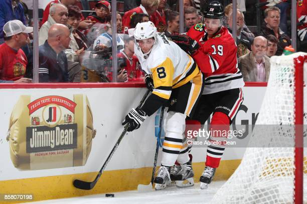 Brian Dumoulin of the Pittsburgh Penguins and Jonathan Toews of the Chicago Blackhawks chase the puck in the second period at the United Center on...