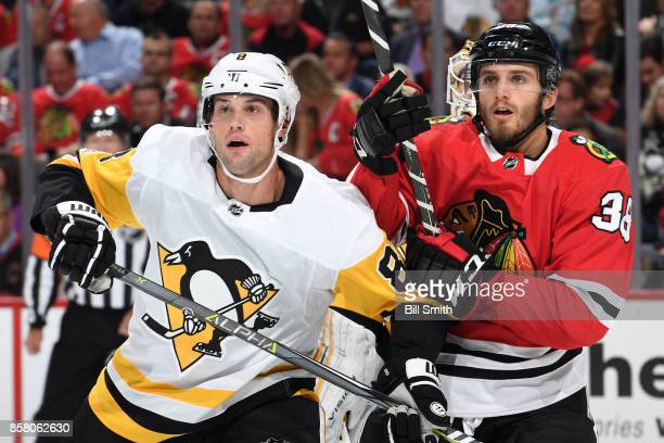 Brian Dumoulin of the Pittsburgh Penguins and Ryan Hartman of the Chicago Blackhawks watch for the puck in the first period at the United Center on...
