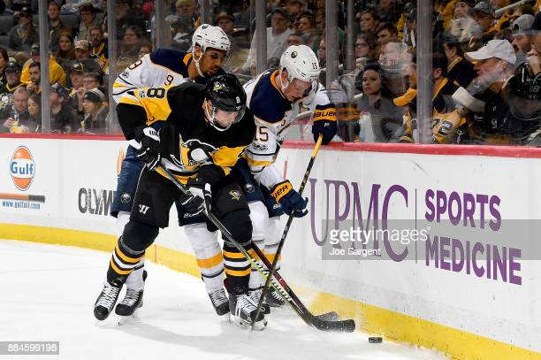 Brian Dumoulin of the Pittsburgh Penguins battles for the puck against Jack Eichel of the Buffalo Sabres and Evander Kane of the Buffalo Sabres at...