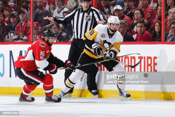 Brian Dumoulin of the Pittsburgh Penguins chips the puck past Clarke MacArthur of the Ottawa Senators in Game Four of the Eastern Conference Final...