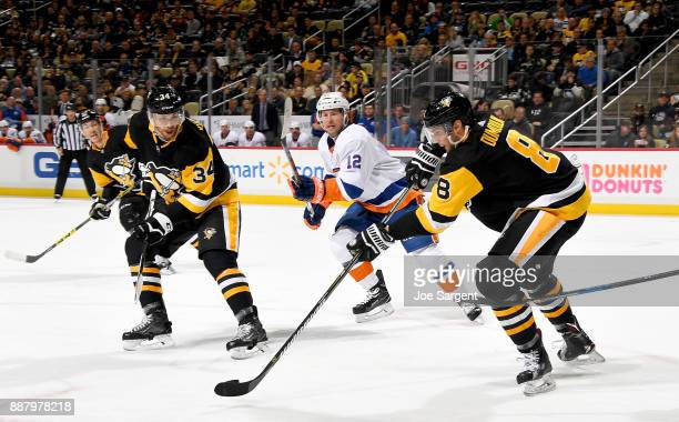 Brian Dumoulin of the Pittsburgh Penguins moves a puck against Josh Bailey of the New York Islanders at PPG Paints Arena on December 7 2017 in...