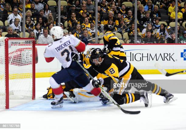 Brian Dumoulin of the Pittsburgh Penguins pushes Vincent Trocheck of the Florida Panthers at PPG PAINTS Arena on October 14 2017 in Pittsburgh...
