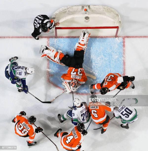Brian Elliot of the Philadelphia Flyers covers the puck as teammates Mark Alt Travis Sanheim Sean Couturier#14 and Claude Giroux battles against...