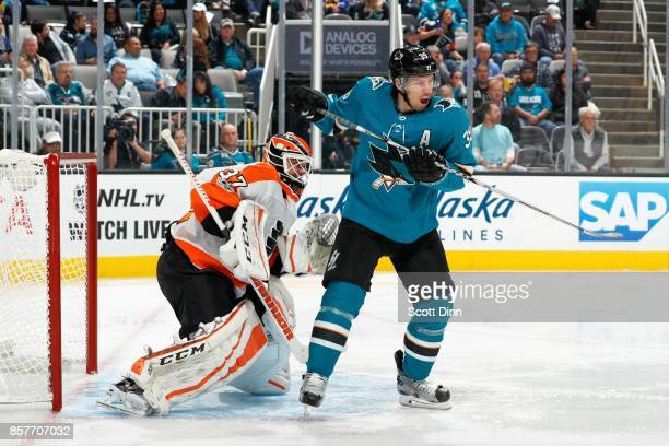 Brian Elliot of the Philadelphia Flyers defends against Logan Couture of the San Jose Sharks during a NHL game at SAP Center at San Jose on October 4...