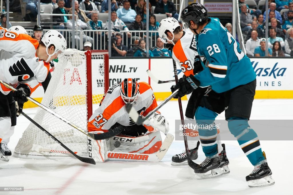 Brian Elliot #37 of the Philadelphia Flyers makes a save as Shayne Gostisbehere #53 of the Philadelphia Flyers and Timo Meier #28 of the San Jose Sharks look during a NHL game at SAP Center at San Jose on October 4, 2017 in San Jose, California.