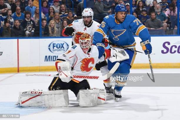 Brian Elliott and Matt Bartkowski of the Calgary Flames defend against Ryan Reaves of the St Louis Blues on March 25 2017 at Scottrade Center in St...