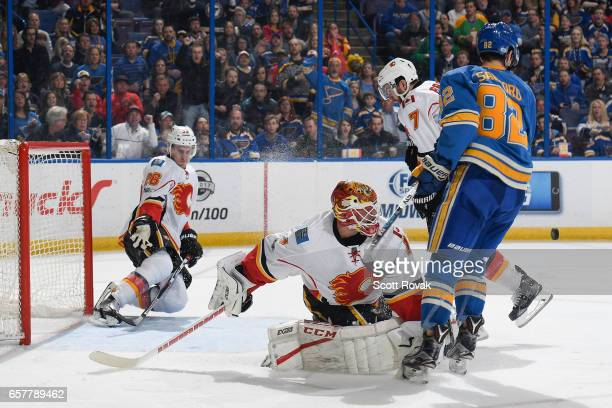 Brian Elliott and TJ Brodie of the Calgary Flames defends against Zach Sanford of the St Louis Blues as Michael Stone of the Calgary Flames defends...