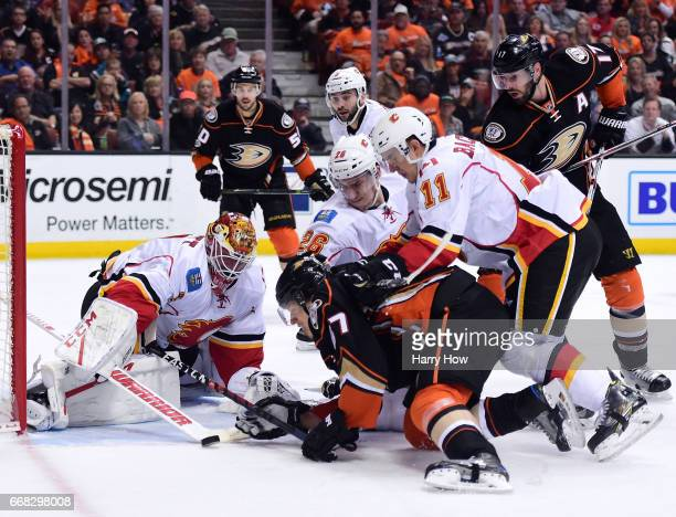 Brian Elliott of the Calgary Flames makes a save as Rickard Rakell of the Anaheim Ducks looks for a rebound with and Mikael Backlund and Michael...