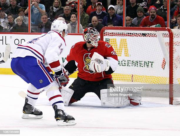 Brian Elliott of the Ottawa Senators looks over his shoulder at the puck as Tomas Plekanec of the Montreal Canadiens scores a secondperiod goal at...