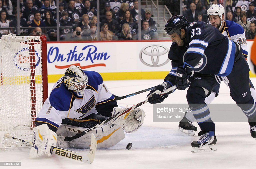 <a gi-track='captionPersonalityLinkClicked' href=/galleries/search?phrase=Brian+Elliott&family=editorial&specificpeople=687032 ng-click='$event.stopPropagation()'>Brian Elliott</a> #1 of the St. Louis Blues blocks a shot on goal by <a gi-track='captionPersonalityLinkClicked' href=/galleries/search?phrase=Dustin+Byfuglien&family=editorial&specificpeople=672505 ng-click='$event.stopPropagation()'>Dustin Byfuglien</a> #33 of the Winnipeg Jets in second-period action of an NHL game at the MTS Centre on October 18, 2013 in Winnipeg, Manitoba, Canada.
