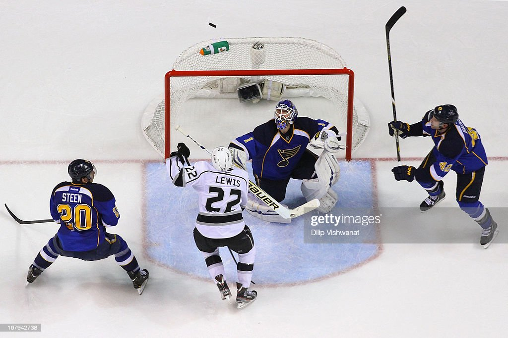 <a gi-track='captionPersonalityLinkClicked' href=/galleries/search?phrase=Brian+Elliott&family=editorial&specificpeople=687032 ng-click='$event.stopPropagation()'>Brian Elliott</a> #1 of the St. Louis Blues keeps his eyes on the puck as <a gi-track='captionPersonalityLinkClicked' href=/galleries/search?phrase=Trevor+Lewis&family=editorial&specificpeople=543187 ng-click='$event.stopPropagation()'>Trevor Lewis</a> #22 of the Los Angeles Kings looks to knock the puck down in Game Two of the Western Conference Quarterfinals during the 2013 NHL Stanley Cup Playoffs at the Scottrade Center on May 2, 2013 in St. Louis, Missouri. The Blues beat the Kings 2-1.