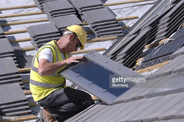 Brian Evans of SolarCentury fits solar tiles to the roof of a residential property in Croydon Surrey UK on Tuesday Aug 7 2007 The tiles will supply...
