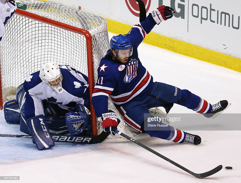 Brian Flynn is tripped up in front of goaltender Drew MacIntyre as the Toronto Marlies play the Rochester Americans at Ricoh Coliseum.