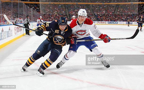 Brian Flynn of the Buffalo Sabres and Nathan Beaulieu of the Montreal Canadiens battle as they skate to the corner boards on November 5 2014 at the...
