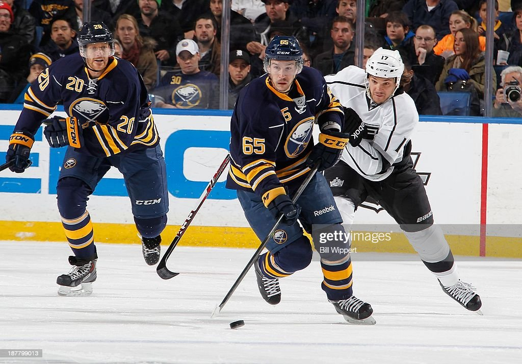 Brian Flynn #65 of the Buffalo Sabres carries the puck in front of Daniel Carcillo #17 of the Los Angeles Kings and Henrik Tallinder #20 of the Sabres on November 12, 2013 at the First Niagara Center in Buffalo, New York.