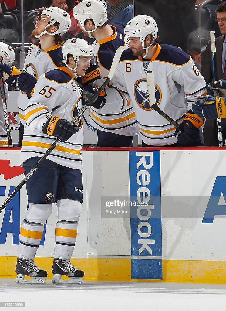 Brian Flynn #65 of the Buffalo Sabres is congratulated by his teammates after scoring his first NHL goal against the New Jersey Devils during the game at the Prudential Center on March 7, 2013 in Newark, New Jersey.