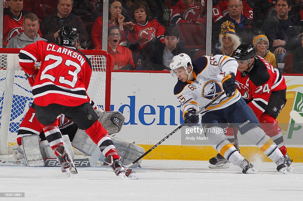 Brian Flynn #65 of the Buffalo Sabres puts the puck past <a gi-track='captionPersonalityLinkClicked' href=/galleries/search?phrase=Johan+Hedberg&family=editorial&specificpeople=202078 ng-click='$event.stopPropagation()'>Johan Hedberg</a> #1 of the New Jersey Devils for his first NHL goal during the game at the Prudential Center on March 7, 2013 in Newark, New Jersey.