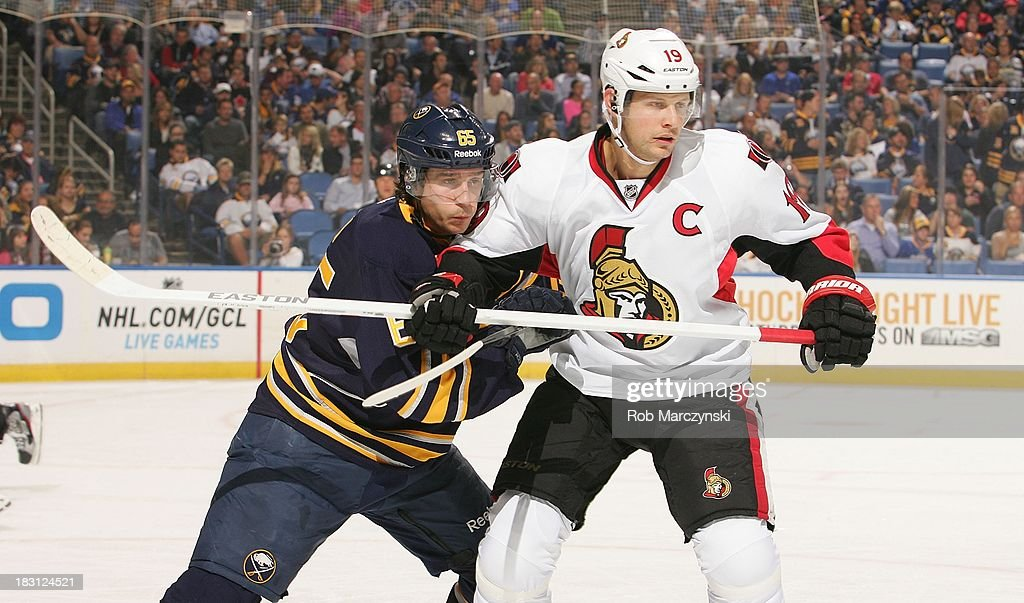 Brian Flynn #65 of the Buffalo Sabres ties up Jason Spezza #19 of the Ottawa Senators on October 4, 2013 at the First Niagara Center in Buffalo, New York.