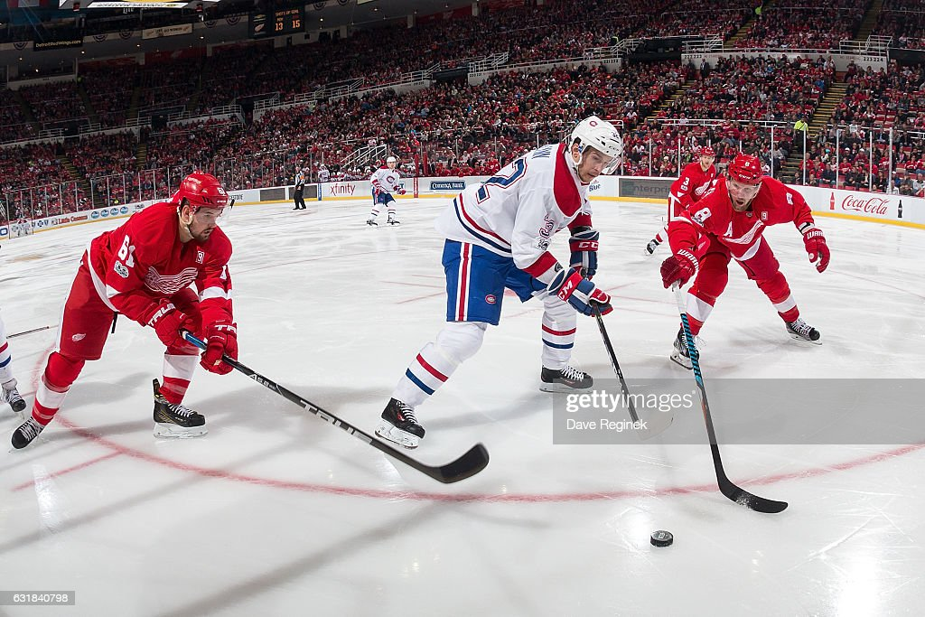 Brian Flynn #32 of the Montreal Canadiens battles for the puck with Justin Abdelkader #8 and Xavier Ouellet #61 of the Detroit Red Wings during an NHL game at Joe Louis Arena on January 16, 2017 in Detroit, Michigan. The Wings defeated the Canadiens 1-0.