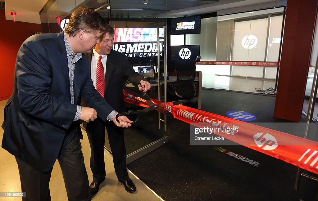 Brian France, NASCAR Chairman and CEO, and Stephen DeWitt, Hewlett Packard Senior Vice President Enterprise, cut the ceremonial ribbon to officially open the center during the NASCAR Fan and Media Engagement Center Unveiling at NASCAR Plaza on January 14, 2013 in Charlotte, North Carolina.