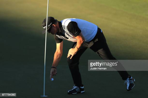 Brian Gay of the United States retrieves his ball after he holed out from 161 yards for eagle on the 18th green during the final round of The RSM...