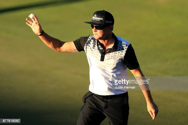 Brian Gay of the United States waves to the crowd after he holed out from 161 yards for eagle on the 18th green during the final round of The RSM...
