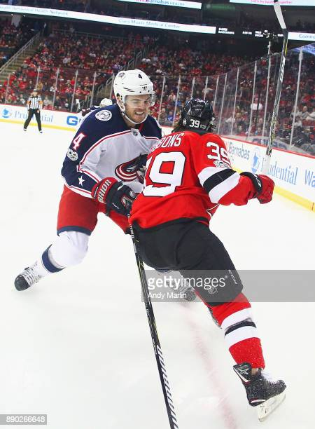 Brian Gibbons of the New Jersey Devils and Scott Harrington of the Columbus Blue Jackets battle for position during the game at Prudential Center on...
