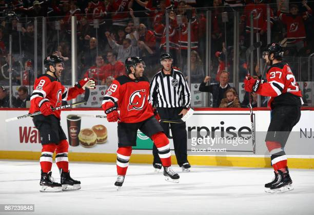 Brian Gibbons of the New Jersey Devils celebrates his second period goal against the Ottawa Senators and is joined by Will Butcher and Pavel Zacha...