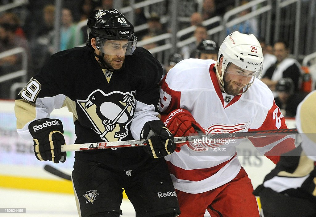 Brian Gibbons # 49 of the Pittsburgh Penguins checks Landon Ferraro # 29 of the Detroit Red Wings during the second period of a preseason game on September 16, 2013 at the CONSOL Energy Center in Pittsburgh, Pennsylvania.