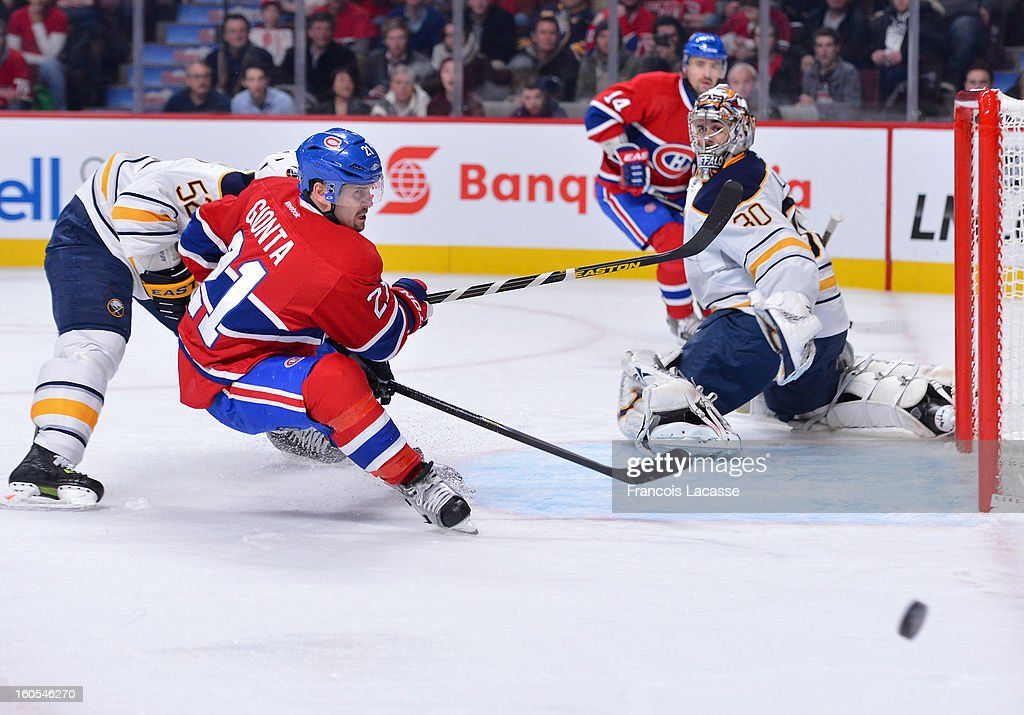 Brian Gionta #21 misses a pass from Tomas Plekanek #14 of the Montreal Canadiens as goaltender Ryan Miller #30 of the Buffalo Sabres kneels on the ice during the NHL game on February 2, 2013 at the Bell Centre in Montreal, Quebec, Canada.