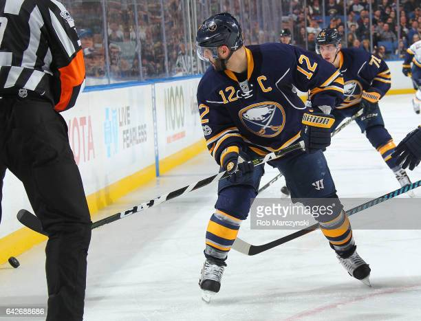 Brian Gionta of the Buffalo Sabres drops a pass to Evan Rodrigues during their NHL game against the St Louis Blues at the KeyBank Center on February...