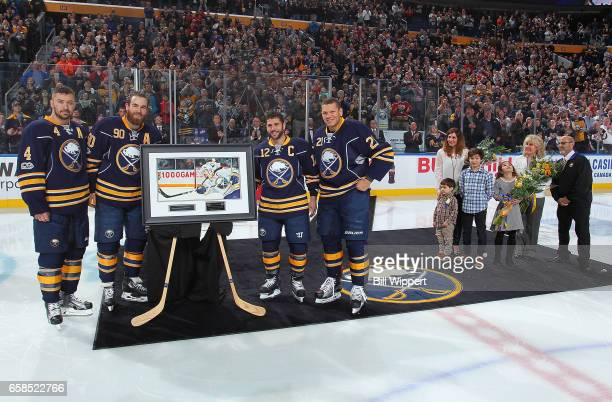 Brian Gionta of the Buffalo Sabres poses with a painting of him alongside teammates Josh Gorges Ryan O'Reilly and Kyle Okposo and his family during a...